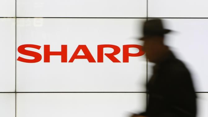 File photo of a pedestrian walking past a logo of Sharp Corp at a train station in Tokyo