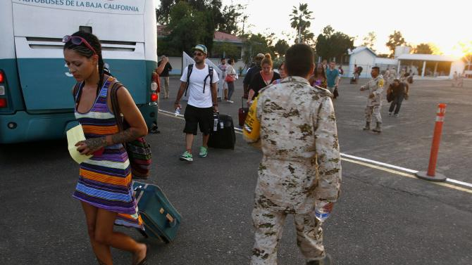Stranded tourists walk past soldiers after being airlifted by the Mexican Army from Los Cabos, at the international airport of Tijuana