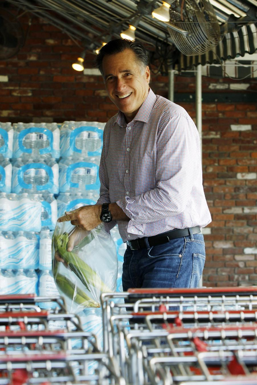 Republican presidential candidate, former Massachusetts Gov. Mitt Romney puts ears of corn into a plastic bag as he arrives at Hunter's Shop and Save supermarket in Wolfeboro, N.H., Monday, Aug. 6, 2012. (AP Photo/Charles Dharapak)