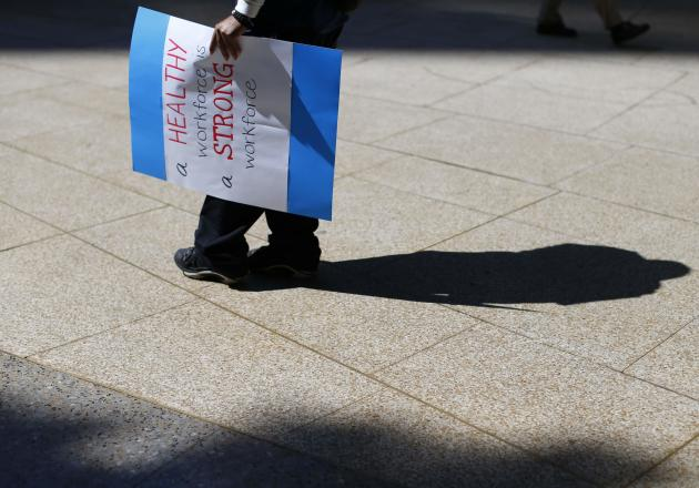 A supporter walks away holding a sign following a rally in San Diego