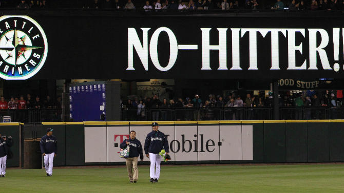 """Seattle Mariners head in from the bullpen as a sign flashes """"No-Hitter!!"""" behind after a baseball game against the Los Angeles Dodgers Friday, June 8, 2012, in Seattle. The Mariners won 1-0 in a six-pitcher combined no-hitter. (AP Photo/Elaine Thompson)"""