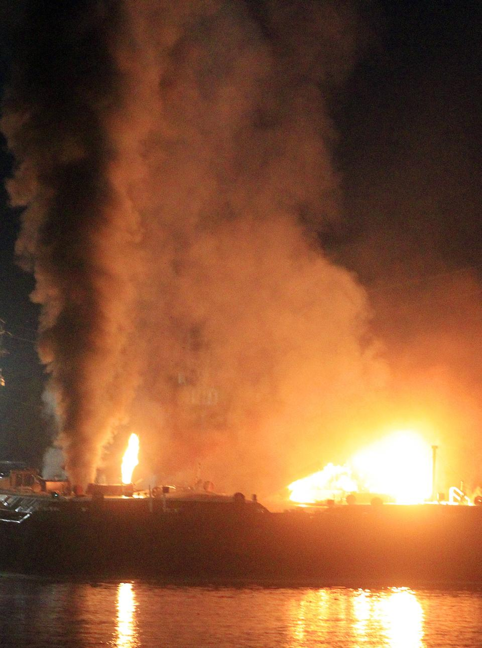 Fire burns aboard two fuel barges along Mobile River after explosions sent three workers to the hospital. Fire officials have pulled units back from fighting the fire due to the explosions and no immediate threat to lives. (AP Photo/Press Register, Glenn Baeske)