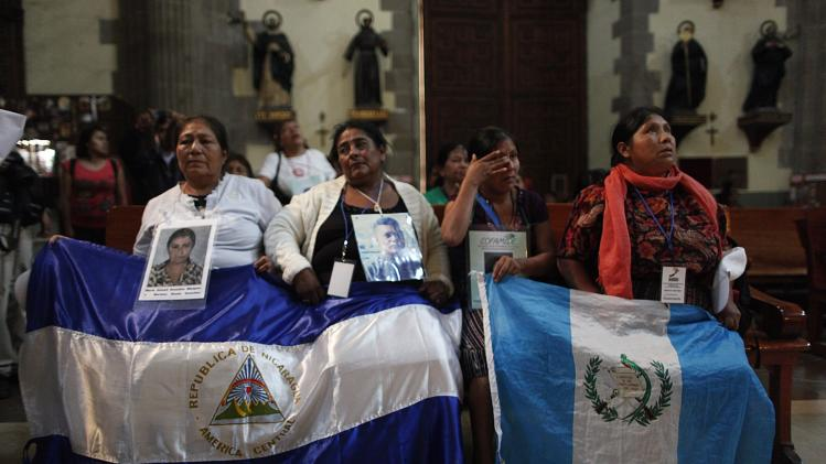 Women from the Caravan of Central American Mothers hold up photos of missing migrants while praying inside Metropolitan Cathedral in Mexico City