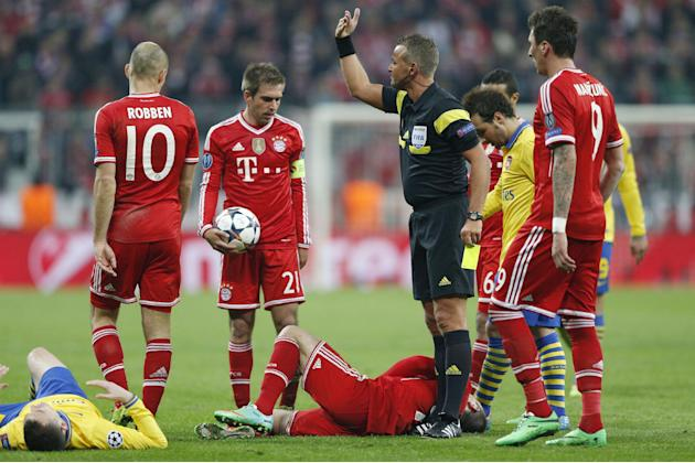Referee Svein Odvar Moen from Norway, center, calls in support after Bayern's Franck Ribery, bottom center, was fouled by Arsenal's Thomas Vermaelen, left, during the Champions League round of