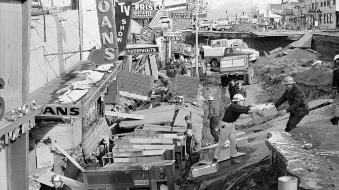 File - In this March 30, 1964 file photo, Anchorage small business owners were going full tilt clearing salvagable items and equipment from their earthquake-ravaged stores on shattered Fourth Avenue in Alaska, in the aftermath of an earthquake. North America's largest earthquake rattled Alaska 50 years ago, killing 15 people and creating a tsunami that killed 124 more from Alaska to California. The magnitude 9.2 quake hit at 5:30 p.m. on Good Friday, turning soil beneath parts of Anchorage into jelly and collapsing buildings that were not engineered to withstand the force of colliding continental plates. (AP Photo, File)