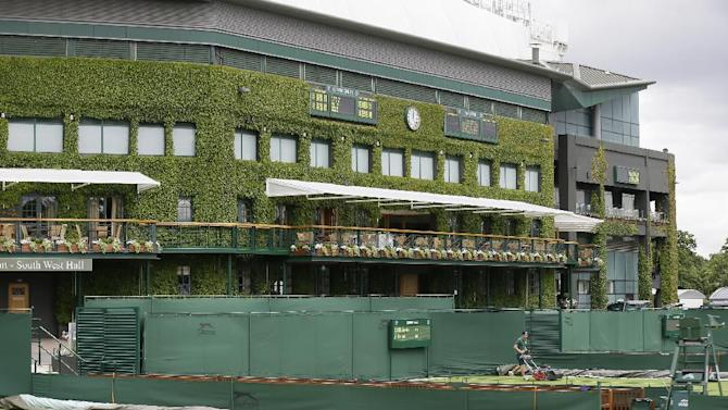 Groundsmen make final preparations on the outside courts backdropped by Centre Court, for the start of the Wimbledon tennis championships in London, Sunday, June 23, 2013. The Wimbledon Championships start Monday, with defending men's champion Roger Federer of Switzerland attempting to win the title for the eighth time. (AP Photo/Alastair Grant)