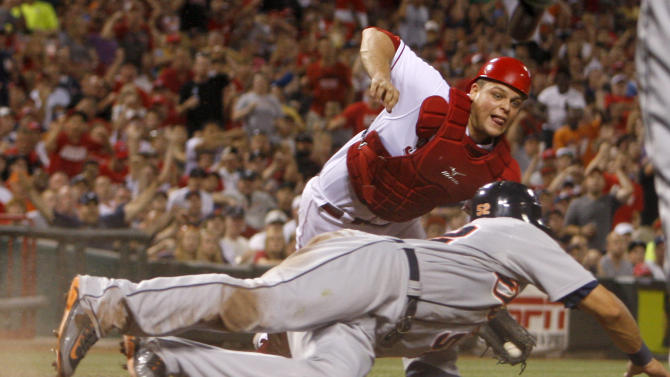 Detroit Tigers' Quintin Berry, bottom, is safe at home beating the tag from Cincinnati Reds catcher Devin Mesoraco, top, after a single hit by Prince Fielder in the seventh inning during a baseball game, Sunday, June 10, 2012, in Cincinnati. The Tigers won 7-6. (AP Photo/David Kohl)