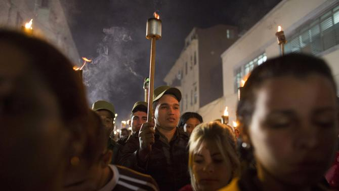 Cuban soldiers hold torches during a march in celebration of the 162nd birth anniversary of Cuba's independence hero Jose Marti, in Havana