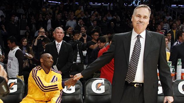 Los Angeles Lakers head coach Mike D'Antoni (R) shakes hands with Kobe Bryant (L) before making his coaching game debut with the Lakers in their NBA basketball game against the Brooklyn Nets (Reuters)