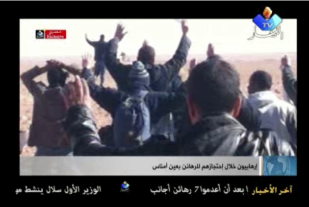 In this image made from video, a group of people believed to be hostages kneel in the sand with their hands in the air at an unknown location in Algeria. Algerian de-mining teams were scouring a gas r