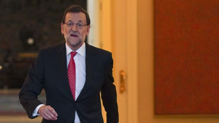 Spain's PM Rajoy reacts as he leaves his office upon greeting Ecuador's President Correa at the Moncloa Palace in Madrid
