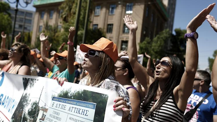 Greek state hospital staff chant slogans as they hold a banner with a photograph of the Aghia Varvara Hospital where they work, in central Athens, on Wednesday, Sept. 4, 2013. Hundreds of state health workers took part in the rally to protest planned mandatory public sector employee transfers and suspensions as part of the government's harsh austerity drive. (AP Photo/Petros Giannakouris)