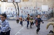 Students play in a school playground in Aleppo's Bustan al-Qasr October 28, 2013. REUTERS/Mahmoud Hassano