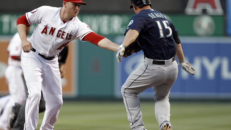 Los Angeles Angels first baseman Mark Trumbo, left, tags out Seattle Mariners' Kyle Seager (15) on a ground ball to the pitcher in the first inning during a baseball game Tuesday, May 21, 2013 in Anaheim.    (AP Photo/Alex Gallardo)