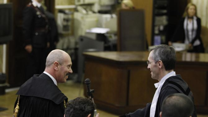 Silvio Berlusconi lawyer Niccolo' Ghedini, right, shakes hands with Prosecutor Fabio De Pasquale after the reading of the verdict for the case where the former Italian Prime Minister Silvio Berlusconi stands accused of bribing  British lawyer David Mills in Milan, Italy, Saturday, Feb. 25, 2012. The court has ruled that the statute of limitations has run out in the corruption case against Silvio Berlusconi, handing Italy's former prime minister another victory in a long string of judicial woes he has faced. (AP Photo/Luca Bruno)
