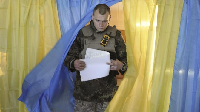 A Ukrainian government forces member walks out of a voting booth during a parliamentary election at a polling station in Novoaidar near Luhansk