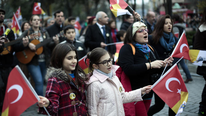 Faithful sing and wave flags as they wait to see Pope Francis visiting Haghia Sofia, the Byzantine church-turned-mosque that is now a museum, in Istanbul, Saturday, Nov. 29, 2014. Pope Francis visits two of Turkey's most iconic sites and shifts gears toward more religious affairs as he arrives in Istanbul for the second leg of his three-day visit to the Muslim nation. (AP Photo/Markus Schreiber)