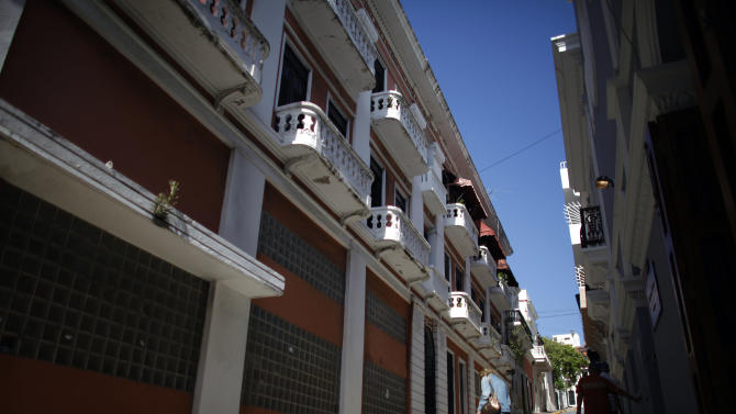 People walk in a street of the historic colonial section of San Juan named Old San Juan in Puerto Rico, Jan. 24, 2013. In recent years, Old San Juan has been on an upswing; its cobblestone streets are cleaner and livelier. New stores, restaurants and coffee shops have opened and many of the old homes have been restored. It's a working city, home to the governor's office and mansion _ said to be the oldest in the western hemisphere _ as well as other government offices and an increasing number of professional firms. It's also become an increasingly busy cruise ship port and outlet and luxury goods shops have proliferated in response. (AP Photo/Ricardo Arduengo)