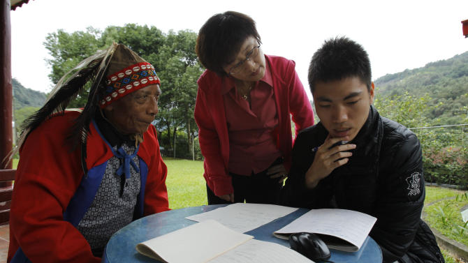 In this photo taken Saturday, Dec. 8, 2012, seventy eight-year-old Angai Kamunuana, left, sits with Taiwanese linguist Sung Li-may, center, and her graduate student documenting his dying tribal language in the aboriginal Kanakanvu mountain village of Dakanua, southern Taiwan. In a race against time, the dedicated linguist is trying to save the historically important aboriginal dialect of Kanakanvu, spoken by only 10 people, from extinction. (AP Photo/Wally Santana)