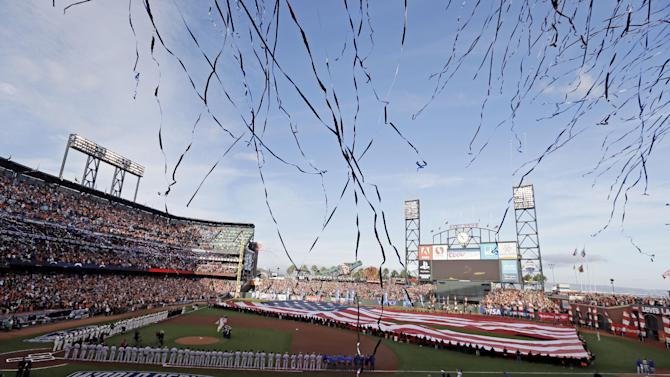 Confetti flies during the national anthem before Game 3 of baseball's World Series between the Kansas City Royals and the San Francisco Giants Friday, Oct. 24, 2014, in San Francisco. (AP Photo/Eric Risberg)