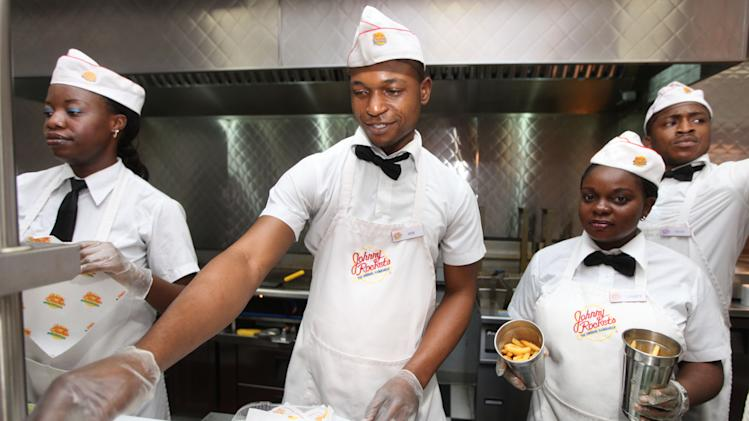 In this photo taken Wednesday, Jan. 23, 2013 workers prepare to serve hamburgers  and fries at Johnny Rockets restaurant in Lagos, Nigeria. As Nigeria's middle class grows along with the appetite for foreign brands in Africa's most populous nation, more foreign restaurants and lifestyle companies are entering the country. And the draw on Nigerians' new discretionary spending has also put new expectations on providing quality service in a nation where many have grown accustomed to expecting very little. ( AP Photo/Sunday Alamba)
