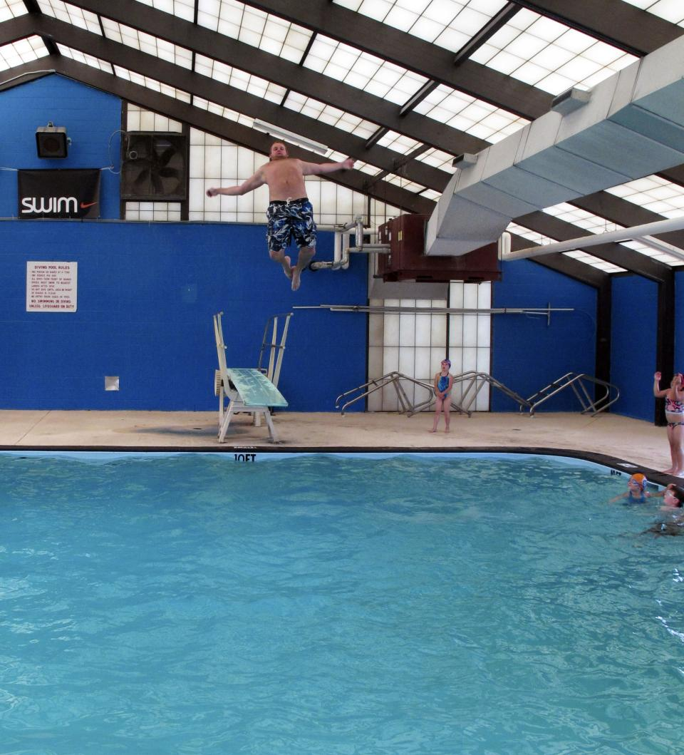 In this May 11, 2011 photo, Anderson Swim Club coach Tommy Starkweather jumps into the Sheppard Swim Center pool to do a giant cannonball, in Anderson, S.C. City officials have closed the pool to the public because of budget woes. (AP Photo/Jeffrey Collins)