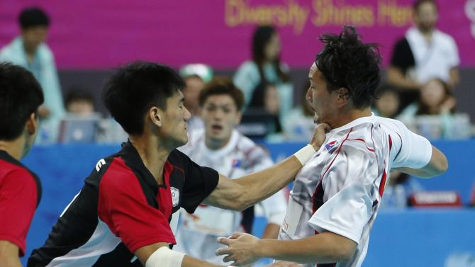 Japan's Hiroki Shida fights for the ball with Taiwan's Hsu Hsien-ming during their men's handball game at the Seonhak Handball Gymnasium during the 17th Asian Games in Incheon