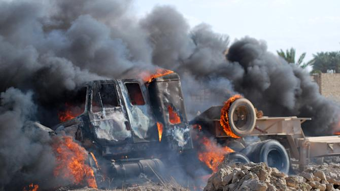 A burning Iraqi army military vehicle near the demonstration site in Ramadi, Iraq, 70 miles (115 kilometers) west of Baghdad, Iraq, Tuesday, April 23, 2013. Protesters threw stones on a military convoy that was passing near the protest site in Ramadi, one army Humvee was flipped over and the soldiers opened fire on the fire, then they left, the protesters set fire on the abandoned army vehicle. Iraqi security forces backed by helicopters raided a Sunni protest camp before dawn Tuesday, prompting clashes that killed at least 36 people in the area and significantly intensified Sunni anger against the Shiite-led government. (AP Photo)