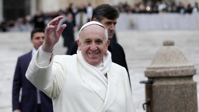 Pope Francis waves as he conducts his weekly general audience at St. Peter's Square at the Vatican