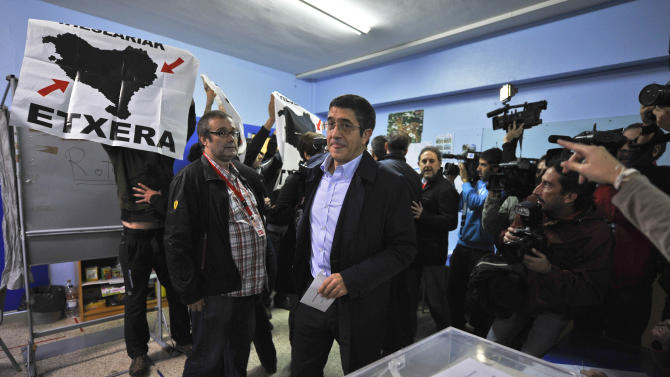"""Basque Regional President or """"Lehendakari"""", Patxi Lopez, center, arrives to vote, in Bilbao, northern Spain, Sunday Oct. 21, 2012, as pro-independence demonstrators display flags calling to return all prisoners of the Basque armed group ETA to the Basque Country. Almost 4.5 million people will go to the polls Sunday in regional elections in Spain's turbulent Basque region and in northwestern Galicia. (AP Photo/Alvaro Barrientos)"""