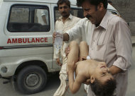 A man carries a child injured in an attack, at a local hospital in Peshawar, Pakistan on Tuesday, Sept 13, 2011. Gunmen attacked a school van in northwestern Pakistan killing three children, the driver and police said. (AP Photo/Mohammad Sajjad)