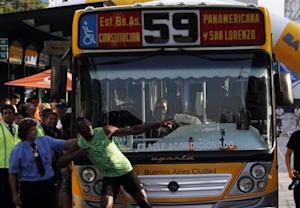 Jamaican sprinter Usain Bolt poses next to the bus driver after competing in a race against a public bus in Buenos Aires