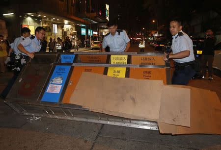 Policemen remove a litter bin after protesters used it as a barricade to block a side street at Mongkok shopping district in Hong Kong