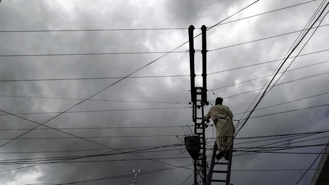 In a Monday, April 30, 2012 photo, a Pakistani municipality worker fixes electrical wires in Abbottabad, Pakistan. One year since U.S. commandos flew into this army town and killed Osama bin Laden, Pakistan has tried to close one of the most notorious chapters in its history. The compound that housed him for six years was razed to the ground, and the wives and children who shared the hideaway were flown to Saudi Arabia just last week. (AP Photo/Muhammed Muheisen)
