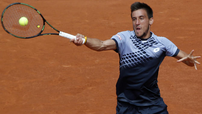 Bosnia and Herzegovina's Damir Dzumhur returns the ball to Switzerland's Roger Federer during their third round match of the French Open tennis tournament at the Roland Garros stadium, Friday, May 29, 2015 in Paris. (AP Photo/Michel Euler)