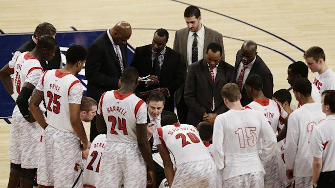 Louisville head coach Rick Pitino, center, talks to his team during the second half of an NCAA college basketball game against Villanova at the Big East Conference tournament, Thursday, March 14, 2013, in New York. Louisville won 74-55. (AP Photo/Frank Franklin II)