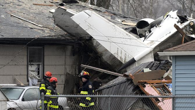 South Bend firefighters work at the scene, Monday, March 18, 2013, the day after a plane crashed near the South Bend Regional Airport, in South Bend, Ind. Two people on the small plane were killed when it clipped one house before slamming into two more Sunday afternoon. (AP Photo/Joe Raymond)