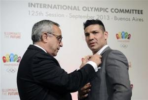 Blanco, President of Madrid 2020 Committee and the Spanish Olympic Committee, gives a pin to WBC middleweight champion Martinez of Argentina after a news conference in Buenos Aires