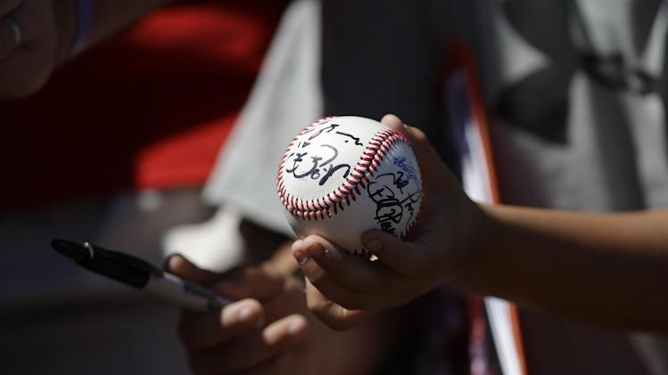 A fan holds an autographed baseball before a spring exhibition baseball game between the Texas Rangers and the Cincinnati Reds Tuesday, March 11, 2014, in Suprise, Ariz. (AP Photo/Darron Cummings)