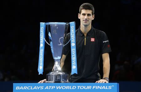 Novak Djokovic of Serbia stands behind the trophy after Roger Federer of Switzerland forfeited due to injury in the men's singles final at the ATP World Tour Finals at the O2 in London