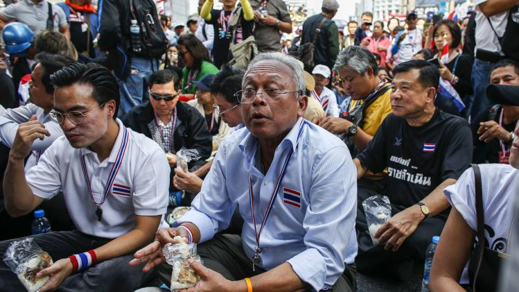 Anti-government protest leader Suthep Thaugsuban sits on a street as he has his lunch during a rally at a major business district in Bangkok