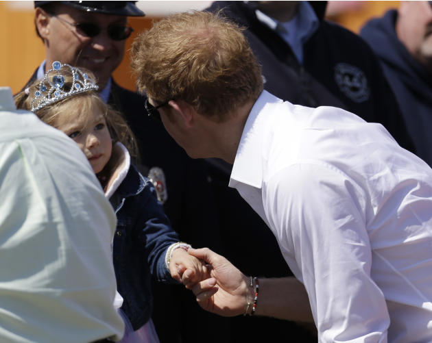 Britain's Prince Harry, right, talks to a young girl at Casino Pier during a tour of the area hit by Superstorm Sandy, Tuesday, May 14, 2013, in Seaside Heights, N.J. The prince toured the community's