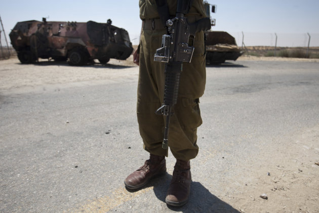 "An Israeli soldier examines the wreckage of an Egyptian military vehicle after militants burst it through a security fence into Israel from Egypt, at an Israeli military base along the border with Egypt, southern Israel, Monday, Aug. 6, 2012. Masked gunmen killed 16 Egyptian soldiers on Sunday, Aug. 5, 2012, at a checkpoint along the border with Gaza and Israel, the first such attack on troops and then the attackers drove off, crashing into Israel, officials said. Egypt blamed Islamist militants from Gaza and Egypt's troubled Sinai Peninsula. President Mohammed Morsi said the attackers ""will pay dearly."" The Israeli military said the attack was part of a plot to abduct an Israeli soldier, and two vehicles commandeered by the attackers crashed into Israel, where one blew up. (AP Photo/Ariel Schalit)"