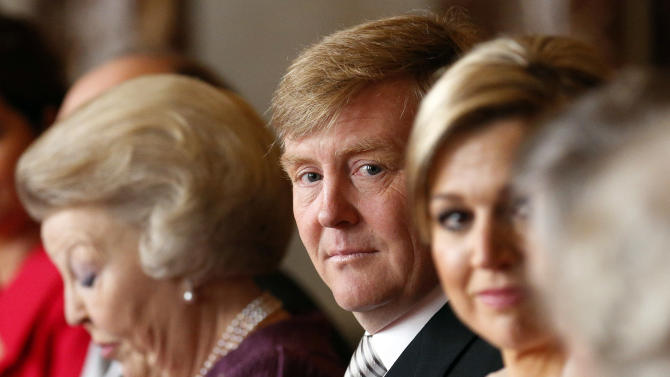 Dutch Queen Beatrix, left, looks down as she prepares to sign the Act of Abdication in favour of her son, Prince Willem-Alexander, center, who sits next to his wife Princess Maxima in the Mozeszaal or Mozes hall of the Royal Palace in Amsterdam, The Netherlands, Tuesday April 30, 2013. Around a million people are expected to descend on the Dutch capital for a huge street party to celebrate the first new Dutch monarch in 33 years. (AP Photo/Michel Porro, pool)
