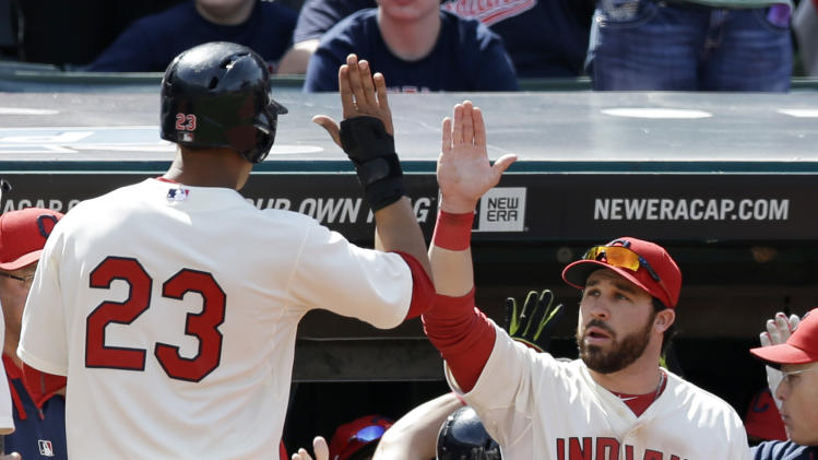 Cleveland Indians' Michael Brantley, left, is congratulated by Jason Kipnis after Brantley scored on a three-run double by David Murphy in the sixth inning of a baseball game against the Toronto Blue Jays, Sunday, April 20, 2014, in Cleveland. (AP Photo/Tony Dejak)