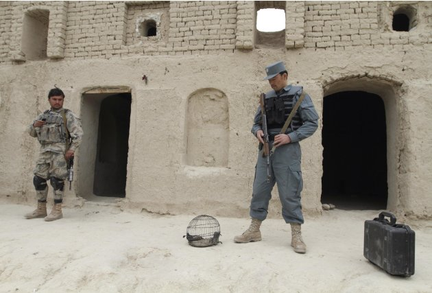 FILE - In this Sunday, March 11, 2012 file photo, Afghan security forces stand guard outside a home where witnesses say Afghans were killed by a U.S. soldier in Panjwai, Kandahar province south of Kab