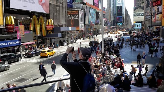 A man takes a photo in New York's Times Square, Thursday, April 25, 2013. The Boston Marathon bombing suspects had planned to blow up their remaining explosives in New York's Times Square, officials said Thursday. (AP Photo/Richard Drew)
