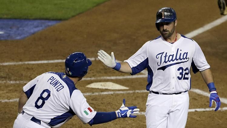 Italy's Tyler LaTorre (32) celebrates with Nick Punto (8) after scoring on a double by Anthony Granato during the second inning of a World Baseball Classic game against the United States on Saturday, March 9, 2013, in Phoenix. (AP Photo/Charlie Riedel)