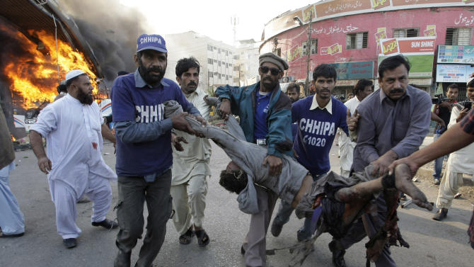 Volunteers carry a wounded bus passenger following a blast in Karachi, Pakistan, Saturday, Dec. 29, 2012. The blast that ripped through the bus set the vehicle on fire and reduced it to little more than a charred skeleton, killing scores of people and leaving many injured. Authorities were trying to determine whether the explosion was caused by a bomb or a gas cylinder, said a police spokesman. (AP Photo/Fareed Khan)