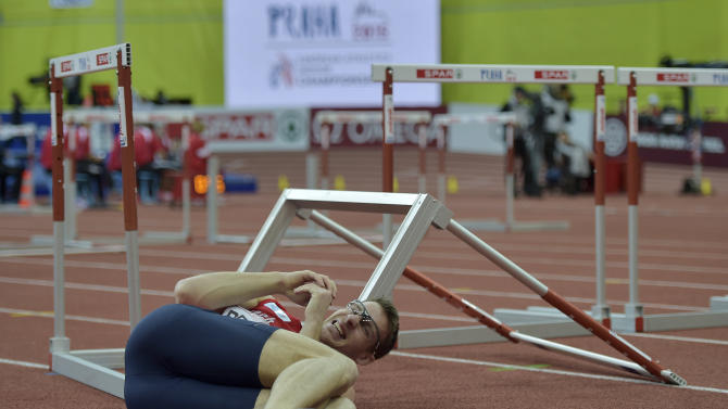 Czech Republic's Petr Penaz sits on the floor after stumbling during a men's 60m hurdles heat at the European Athletics Indoor Championships in Prague, Czech Republic, Friday, March 6, 2015. (AP Photo/Martin Meissner)